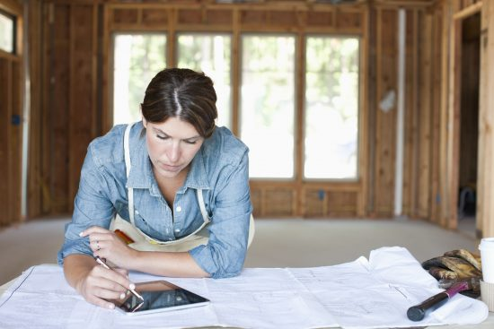 a brunette women looking over plans and an ipad during a renovation