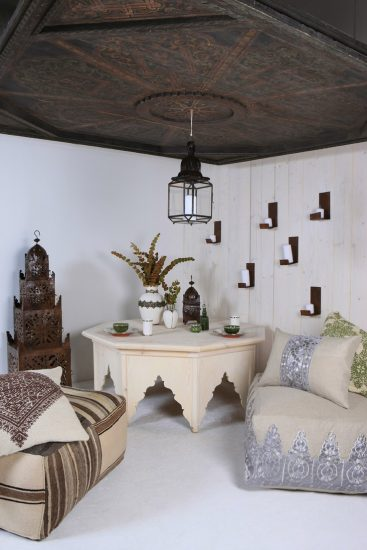 a moroccan themed room with big puff cushions and chairs with a hanging lamp white walls and a dark wood decorative ceiling