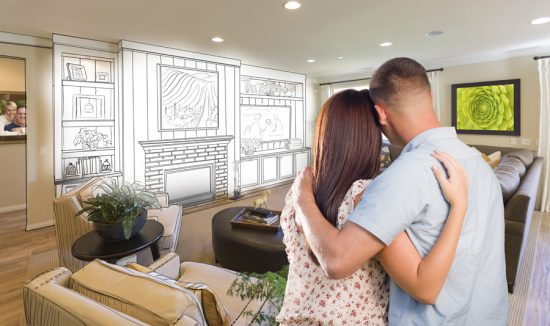 a woman and man embracing as they look at the potential of a newly decorated living room