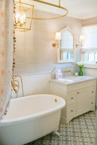 white bathtub, with sink and counter, blue and white decorative tiled floor