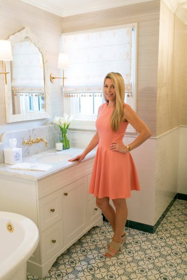 blonde women standing in a cream bathroom with white tile, white tub, sink and finishes