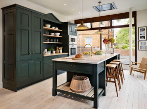 kitchen with black island and dark green cupboard